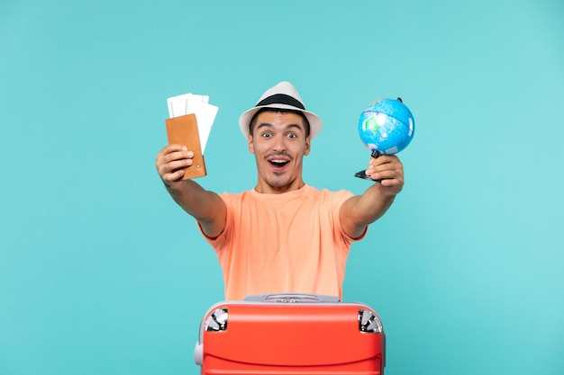 Front view male in vacation holding little globe and tickets excited on blue