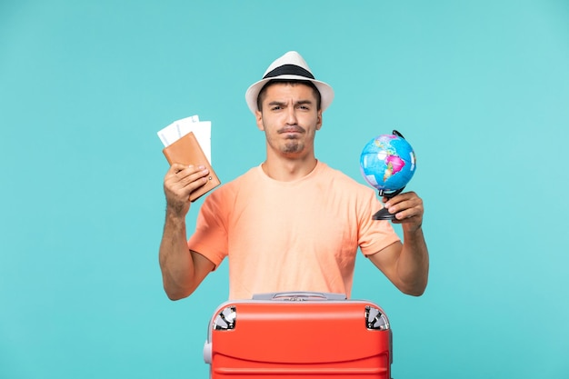 Front view male in vacation holding little globe and tickets on light-blue