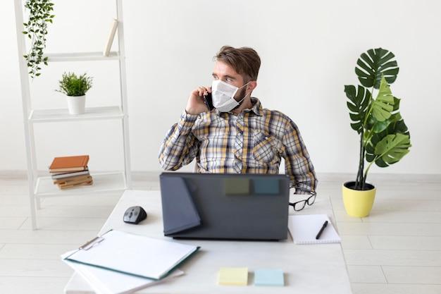 Вид спереди мужчина с маской для лица, работающий из дома