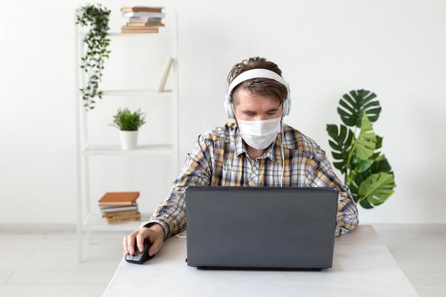 Maschio di vista frontale con maschera facciale che lavora da casa