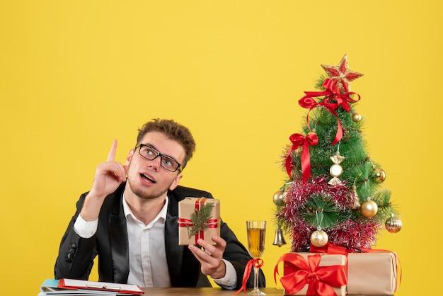 Вид спереди мужчина-работник за своим рабочим местом с подарком на желтом