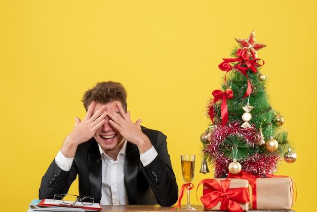 Вид спереди мужчина-работник за своим рабочим местом с подарками, смеясь над желтым