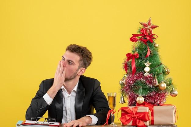 Вид спереди мужчина-работник за своим рабочим местом с подарками на желтом столе, новогодняя работа, рождественский цветной рабочий офис