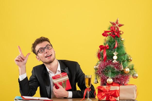 黄色のプレゼントと彼の職場の後ろの正面図の男性労働者