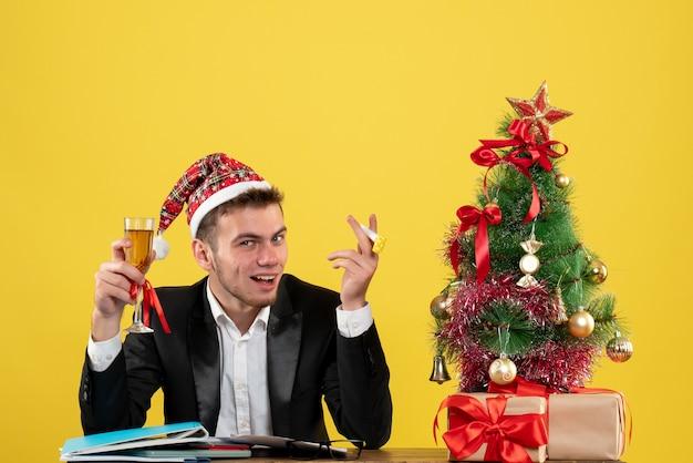 小さなクリスマスツリーの周りにシャンパンでクリスマスを祝う正面図の男性労働者と黄色の机にプレゼント新年のオフィスカラークリスマス