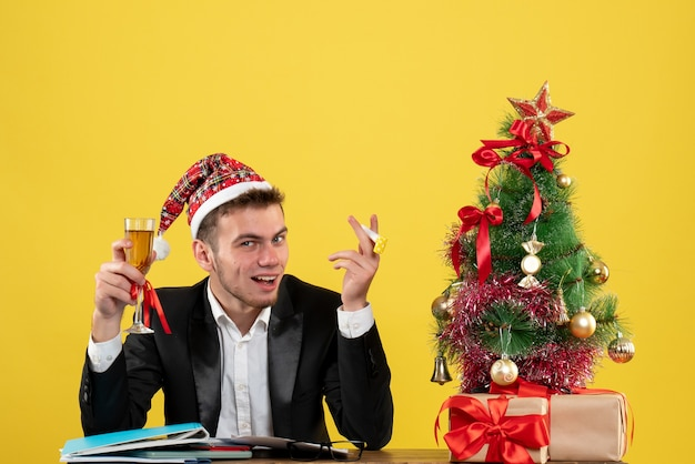 Front view male worker celebrating xmas with champagne around little xmas tree and presents on yellow desk new year office color christmas