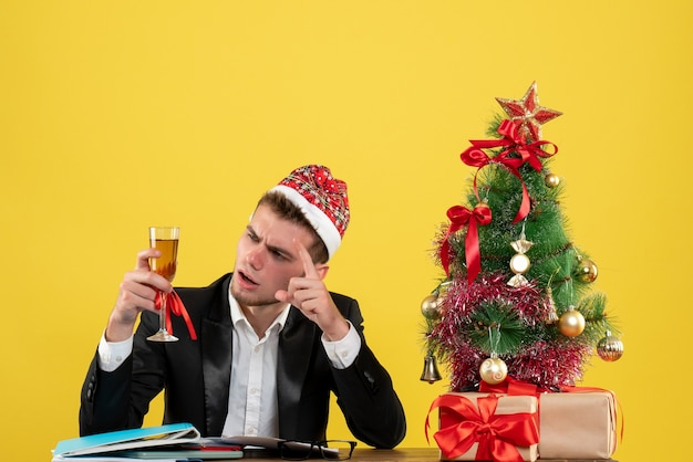 Front view male worker celebrating xmas with champagne around little xmas tree and presents on a yellow