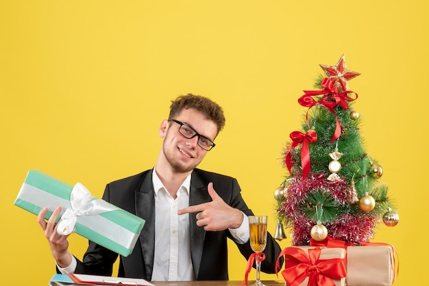 Operaio maschio di vista frontale dietro il suo posto di lavoro che tiene presente nel pacchetto blu su giallo