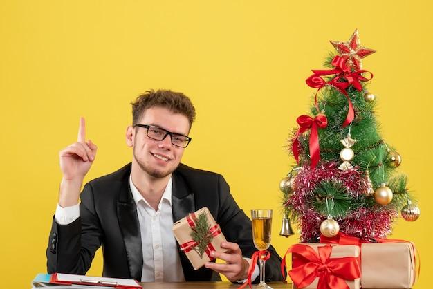 Operaio maschio di vista frontale dietro il suo posto di lavoro che tiene presente sul colore giallo