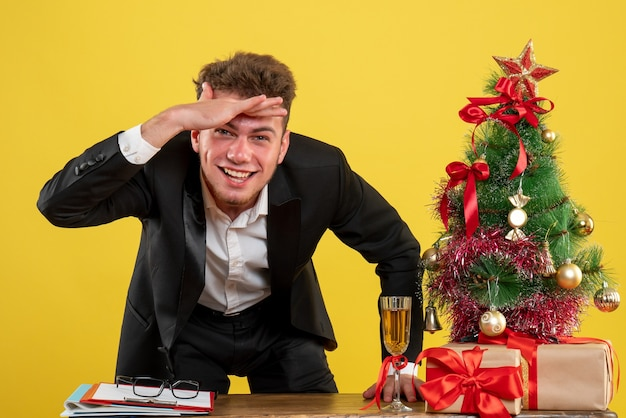 Operaio maschio di vista frontale dietro il suo posto di lavoro che osserva sul colore giallo