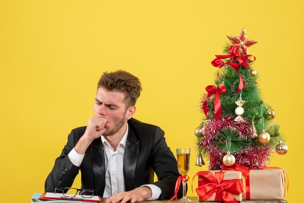Front view male worker behind his working place with presents coughing on yellow