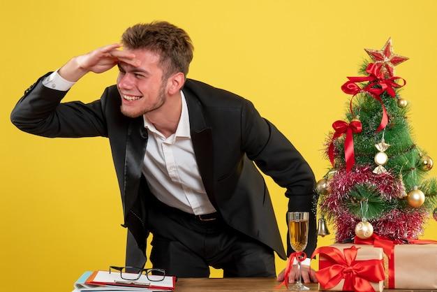 Lavoratore maschio vista frontale dietro il suo posto di lavoro su giallo