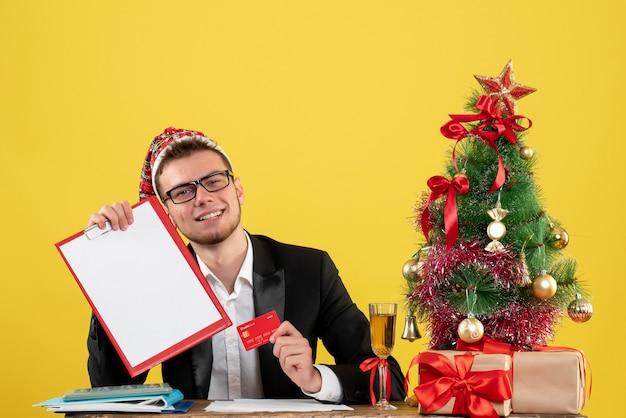 Operaio maschio di vista frontale che tiene la carta di credito intorno al piccolo albero di natale e regali su colore giallo