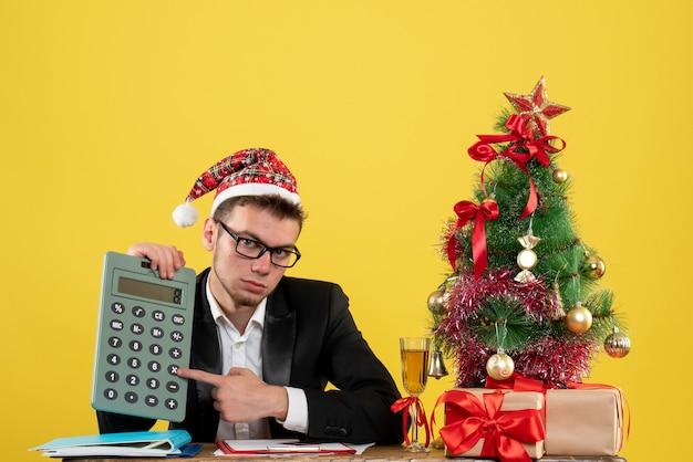Вид спереди мужчина-работник держит калькулятор вокруг маленькой елки и подарки на желтом