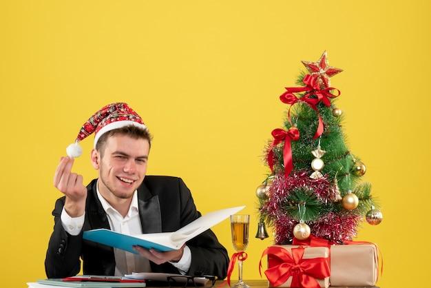 小さなクリスマスツリーの周りにドキュメントを保持し、黄色い机にプレゼント新年のオフィスカラークリスマスの仕事の正面図男性労働者