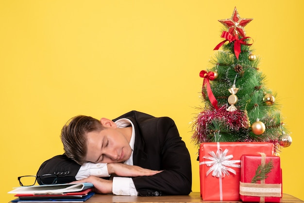 Вид спереди мужчина-работник в костюме, сидя за своим рабочим столом, спит