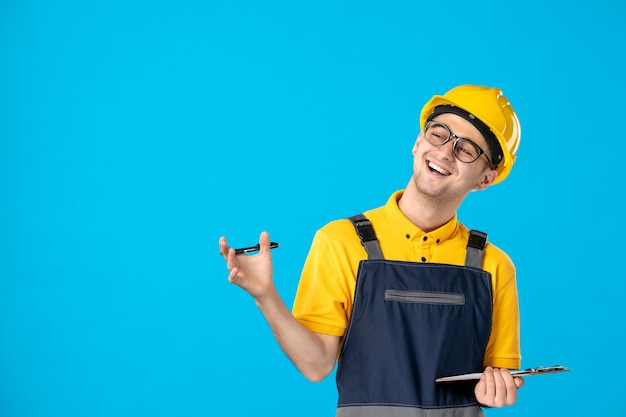 유니폼과 헬멧에 전면보기 남성 노동자 메모 및 파랑에 웃고