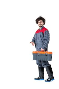 흰 벽에 도구가 있는 가방을 들고 제복을 입은 남성 노동자의 전면