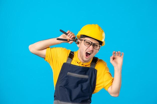 Вид спереди мужчина-работник в униформе, режущий ухо плоскогубцами на синем