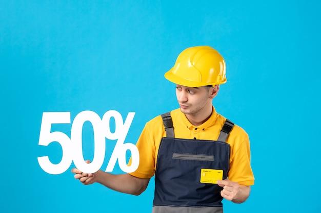 Вид спереди мужчина-работник в форме с письмом и кредитной картой на синем