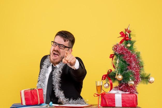 Вид спереди мужчина-работник сидит и празднует рождество на работе, кричит на желтом