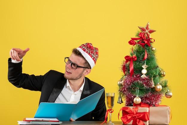 Вид спереди мужчина-работник сидит и читает документы на желтом