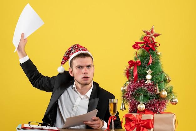 黄色の文書を怒って保持している彼の職場の後ろに座っている正面図の男性労働者