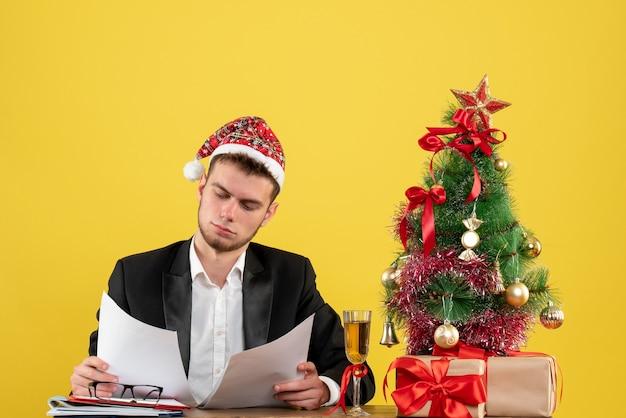 黄色の文書をチェックする彼の職場の後ろに座っている正面図の男性労働者