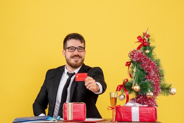 노란색에 은행 카드를 들고 그의 작업 장소 뒤에 앉아 전면보기 남성 노동자