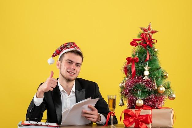黄色の文書を保持している彼の職場の後ろに座っている正面図の男性労働者