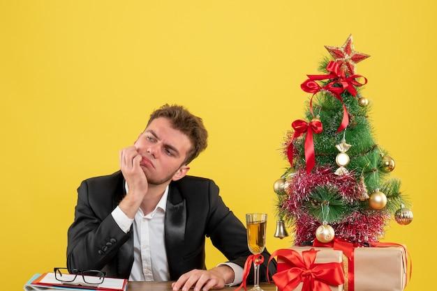 Lavoratore di sesso maschile di vista frontale seduto dietro il suo posto di lavoro pensando sul giallo