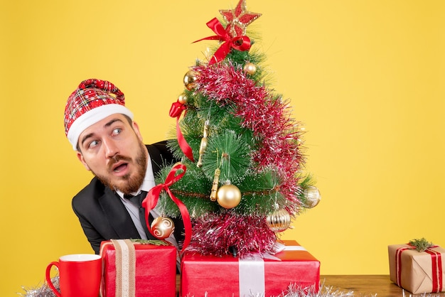Operaio maschio vista frontale seduto dietro il suo posto di lavoro con regali su giallo