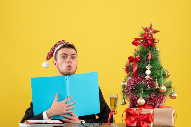 Lavoratore di sesso maschile di vista frontale che si siede e che tiene i documenti su colore giallo