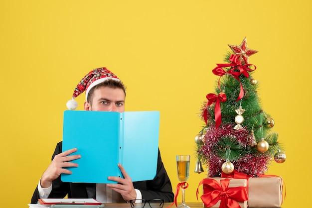 Lavoratore di sesso maschile di vista frontale seduto e leggere i documenti su giallo