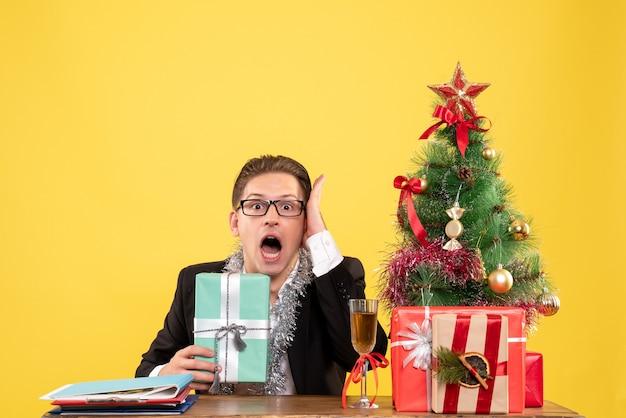 Вид спереди мужчина-работник сидит с рождественскими подарками