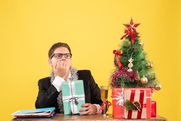 クリスマスプレゼントと一緒に座っている正面図の男性労働者