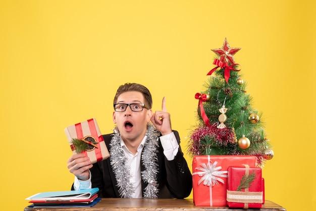 Вид спереди мужчина-работник сидит с подарками