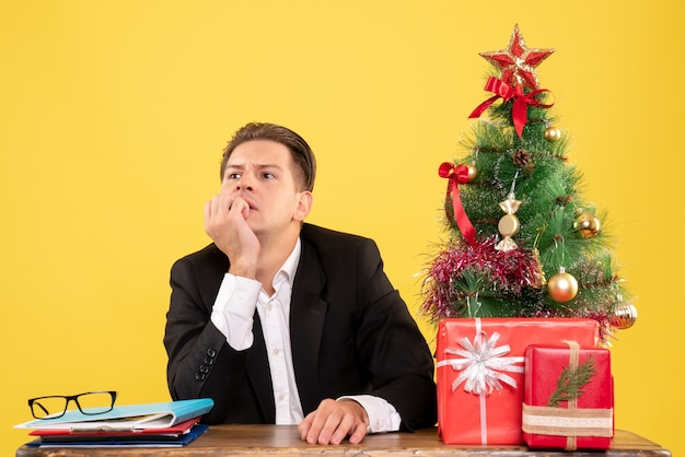 Vista frontale lavoratore maschio in tuta seduto dietro il suo pensiero stressfullu tavolo di lavoro