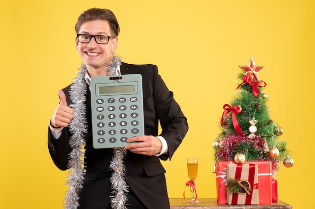 Front view male worker in suit standing and holding calculator