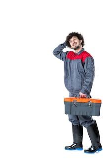 Vista frontale del lavoratore di sesso maschile in uniforme che trasporta la valigia con strumenti sul muro bianco