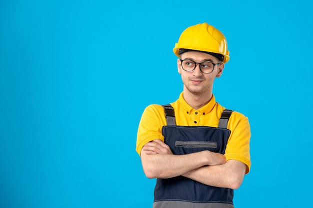 Front view male worker in uniform and helmet looking aside on blue