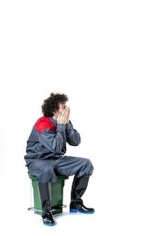 Vista frontale del lavoratore di sesso maschile in uniforme seduto su un piccolo bidone della spazzatura sul muro bianco