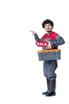Vista frontale del lavoratore di sesso maschile in valigia di strumenti uniformi e scheda di vendita su parete bianca