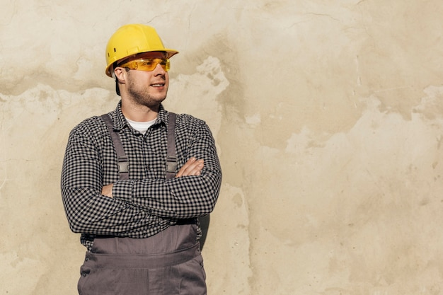 Front view of male worker in uniform with hard hat and protective glasses