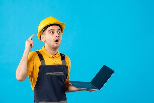 Vista frontale del lavoratore maschio in uniforme con il computer portatile sull'azzurro