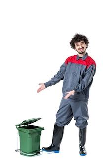 Vista frontale del lavoratore di sesso maschile in uniforme con un piccolo bidone della spazzatura sul muro bianco
