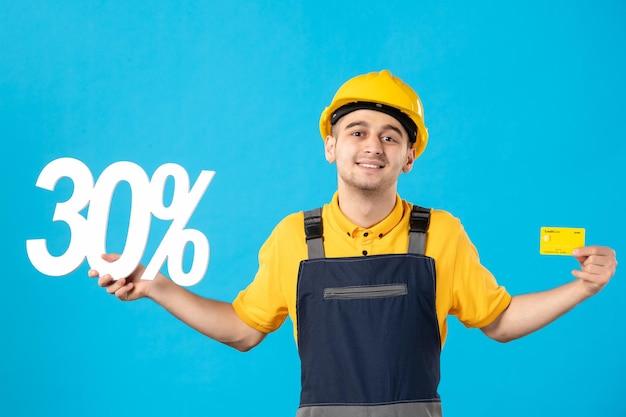 Vista frontale del lavoratore di sesso maschile in uniforme con scritta e carta di credito blu Foto Gratuite