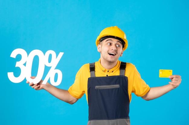 Vista frontale del lavoratore di sesso maschile in uniforme con scritta e carta di credito blu