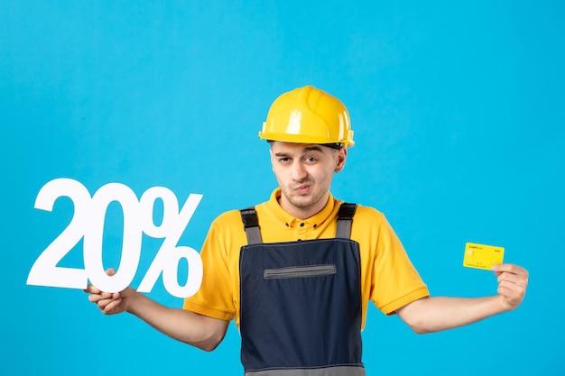 Vista frontale del lavoratore maschio in uniforme con scrittura e carta di credito sull'azzurro