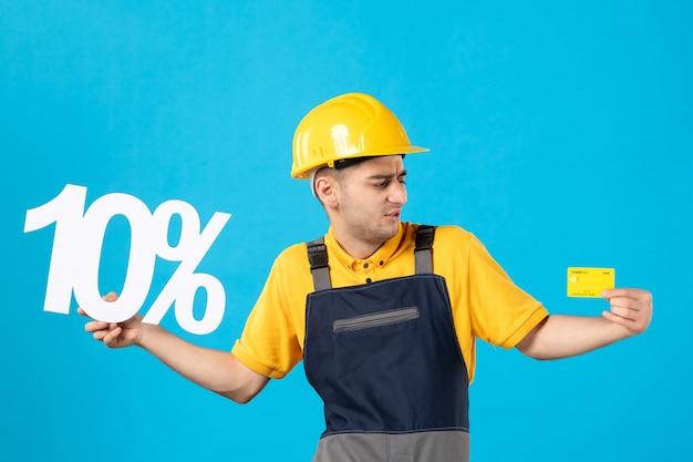 Vista frontale lavoratore maschio in divisa con scritta e carta di credito sull'azzurro